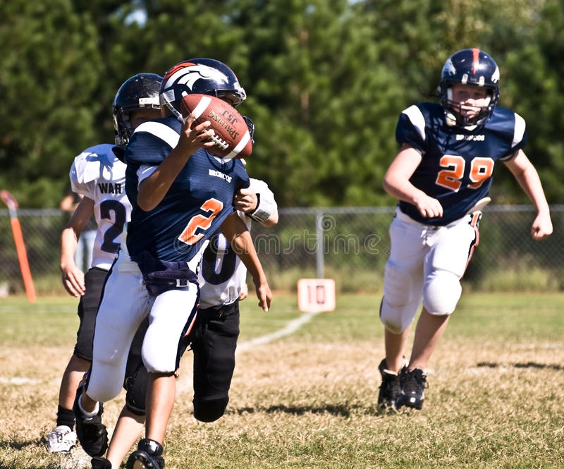 Little League Football Quarterback. A youth league quarterback ready to make a pass at the 10 yard line during a game at the Forsyth County, GA, recreation stock photo