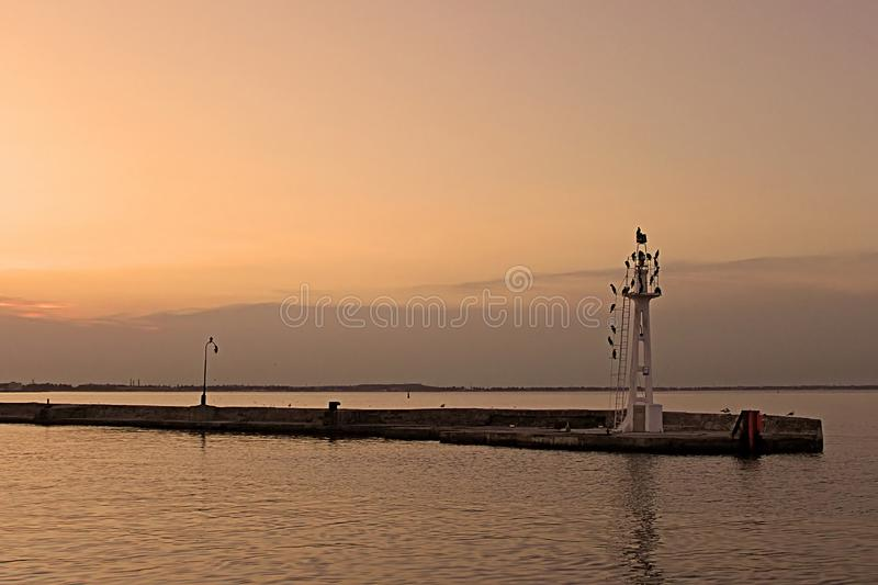 Little lighthouse with birdls in the evening, Odessa, Ukraine royalty free stock photos