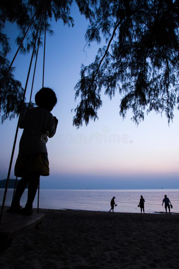 A little local girl playing on the swing on the beach at sunset stock image