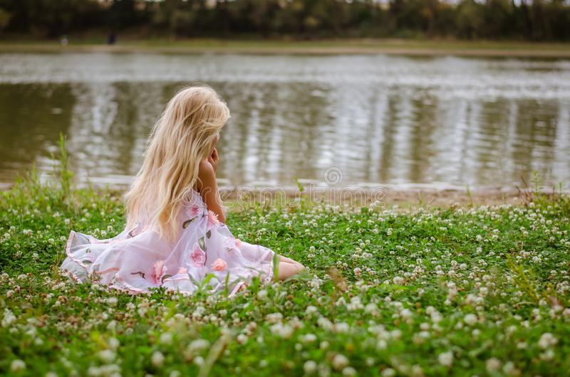 Little lonely girl sitting in the grass by the river stock photography