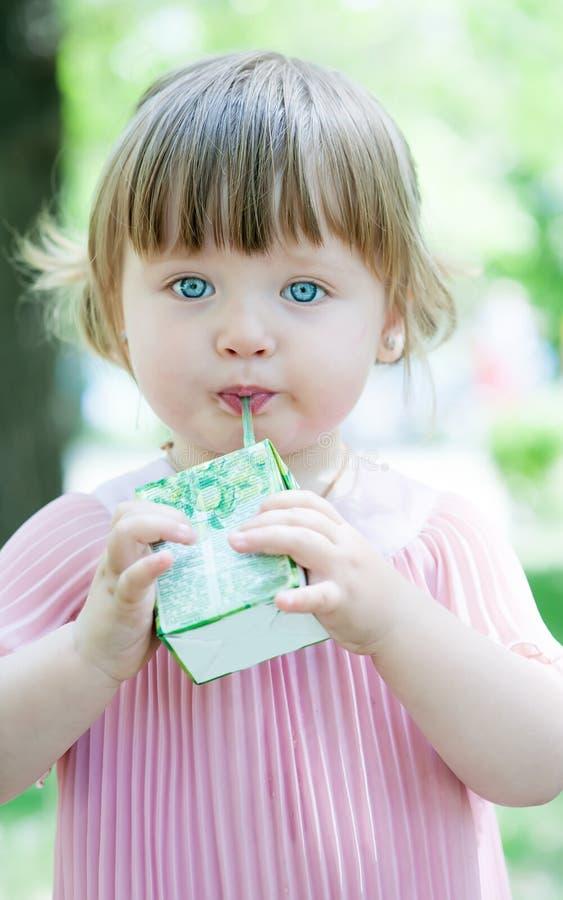Little lovely girl drinking juice stock image