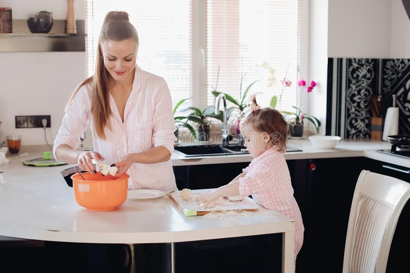 Little lovely kid helping parent with dough at kitchen. Happy wife smiling and preparing breakfast together with child for husband. Beautiful mother with cute royalty free stock images