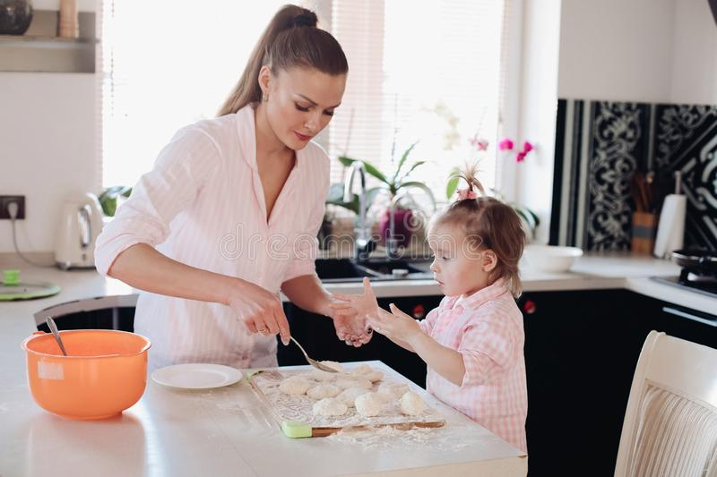 Little lovely kid helping parent with dough at kitchen. Happy wife smiling and preparing breakfast together with child for husband. Beautiful mother with cute royalty free stock photography