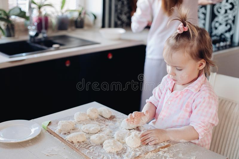 Little lovely kid helping parent with dough at kitchen. Happy wife smiling and preparing breakfast together with child for husband. Beautiful mother with cute royalty free stock photos