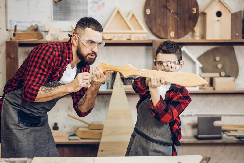Father and little son testing hand-made wood sward evenness at workshop stock photography
