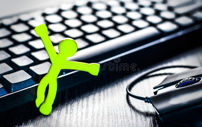 Little man near the computer keyboard and mouse. On the desktop royalty free stock images