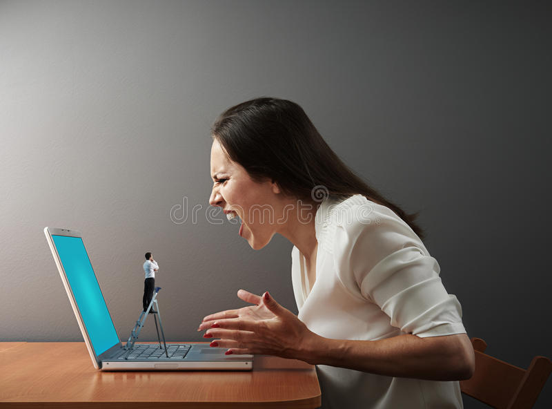 Little man from technical support looking at woman. Little men from technical support looking at screaming women with broken laptop royalty free stock image