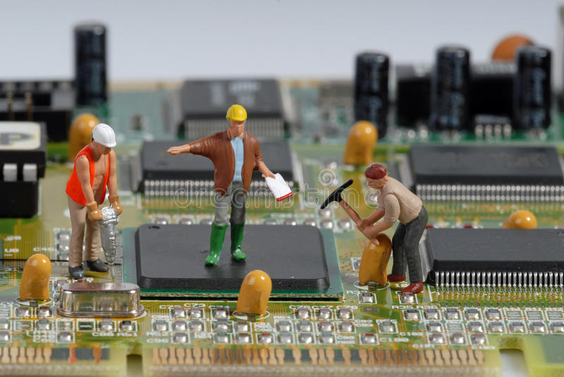 Little men repairing a computer royalty free stock photography