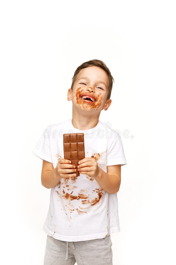 Little messy boy is eating chocolate studio shot royalty free stock photo