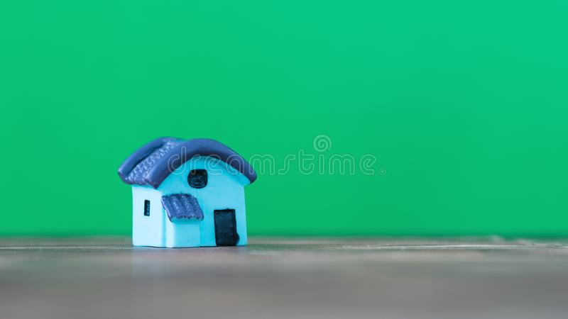 Little miniature house with a blue roof on a wooden table with a green background. The concept of building a new home. royalty free stock photo