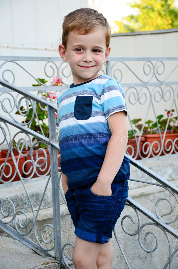 Little model. Beautiful blond smiling little boy posing at the camera near a balcony stock photography