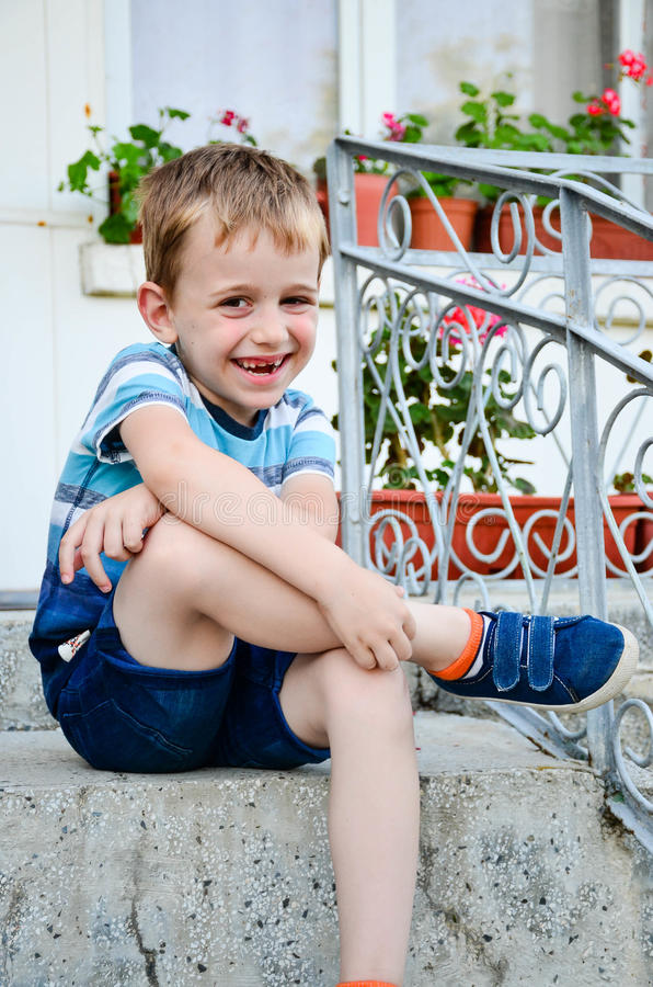 Little model. Beautiful blond smiling little boy without teeth posing at the camera sitting at upstairs stock photo