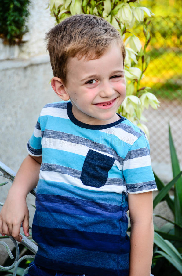 Little model. Beautiful blond smiling little boy without teeth posing at the camera sitting at upstairs royalty free stock photos