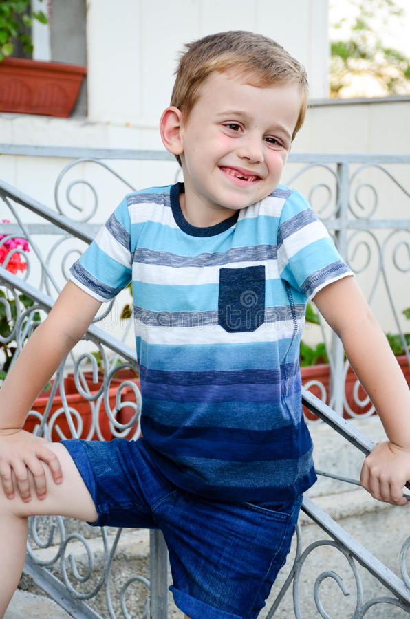 Little model. Beautiful blond smiling little boy without teeth posing at the camera sitting at upstairs stock images