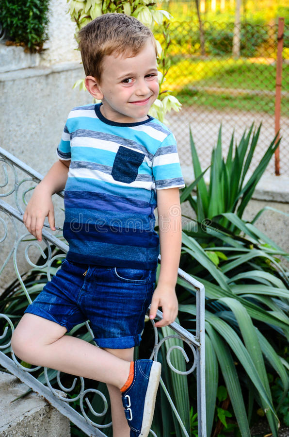 Little model. Beautiful blond smiling little boy without teeth posing at the camera sitting at upstairs royalty free stock image
