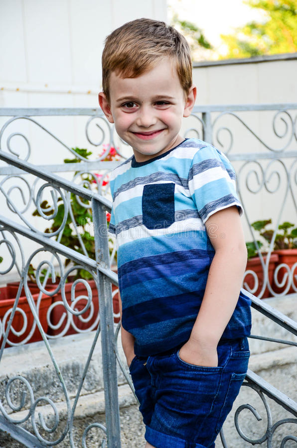 Little model. Beautiful blond smiling little boy without teeth posing at the camera sitting at upstairs stock photography