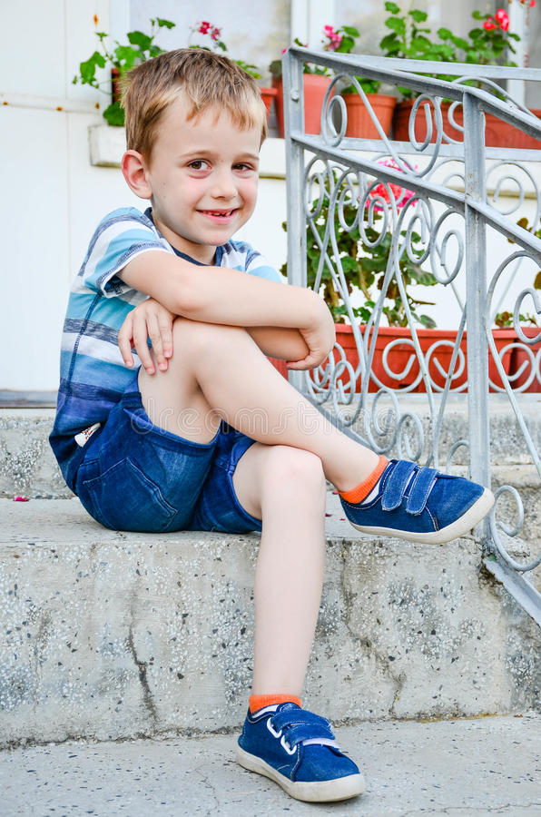 Little model. Beautiful blond smiling little boy without teeth posing at the camera sitting at upstairs stock photos