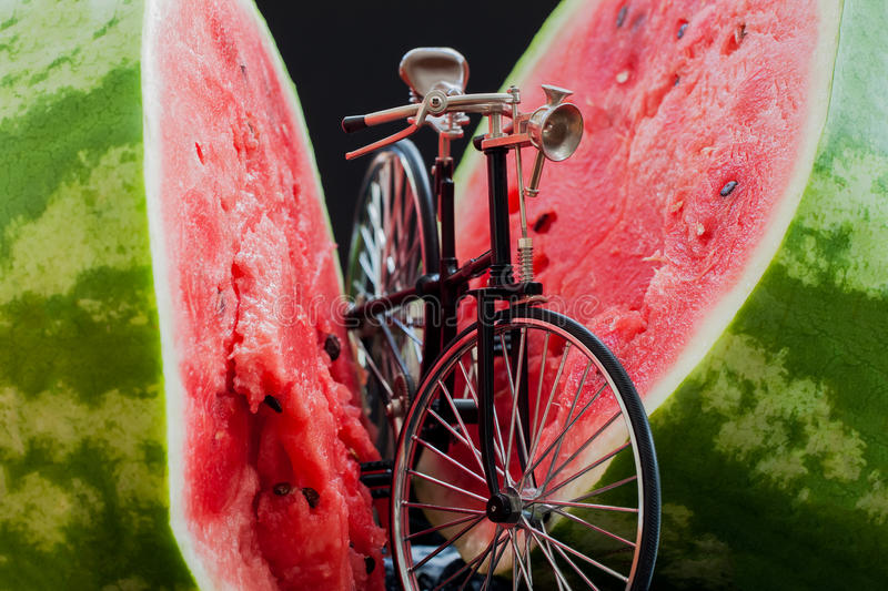 Little model of bicycle near scarlet watermelon. Little model of a retro vintage bicycle near a big cut in half scarlet ripe watermelon royalty free stock photography
