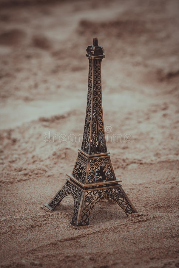 Little model of Eiffel tower on the beach. Little model of Eiffel tower on the beach with vintage effect royalty free stock image