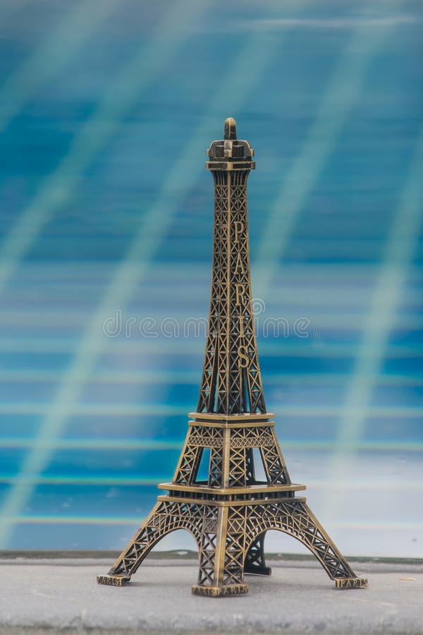 Little model of Eiffel tower and swimming pool background. Little model of Eiffel tower and swimming pool background with vintage effect stock image