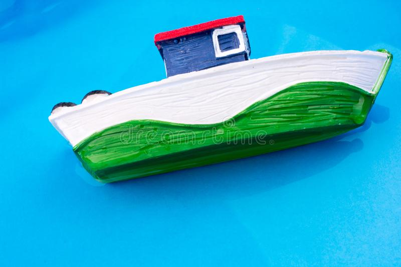 Little model fishing boat grounding one side in water. Little model fishing boat in water on a blue background royalty free stock images