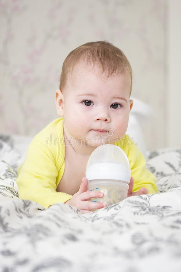 Little 7 months baby girl boy holding a bottle of milk. Cute European Caucasian child in yellow lying on the bed with a bottle,. Vertical portrait of a child stock photos
