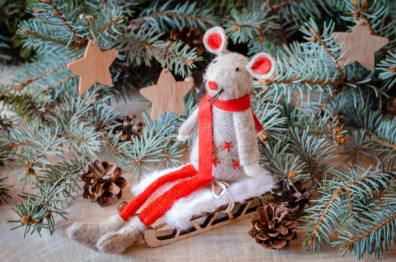 Little mouse or rat toy with a red scarf on a sled. The symbol of Chinese Happy New Year 2020. New year decorations. Little mouse toy with a red scarf on a sled royalty free stock photo