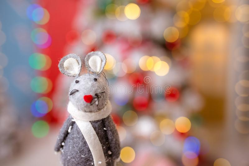 Little mouse toy, symbol of Chinese happy new 2020 in grey dress and new year decoration blur background. Horoscope sign 2020. New stock photography