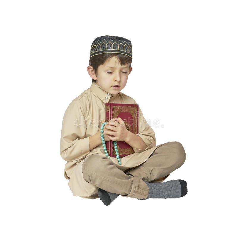 Little muslim boy praying and holding Koran with rosary beads on white background. Muslim Arabic boy praying on white background royalty free stock photo