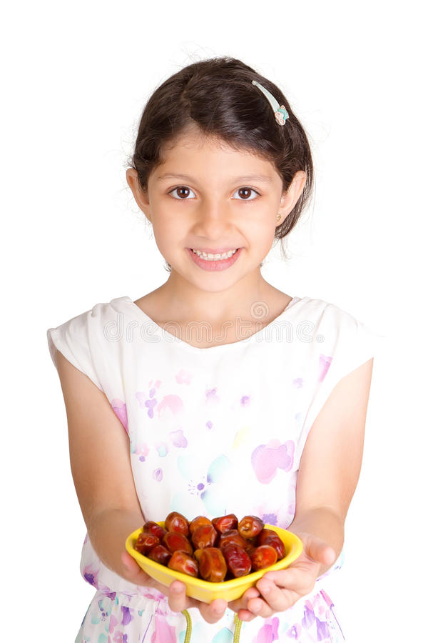 Little Muslim kid presenting a dish of dates for iftar stock photo