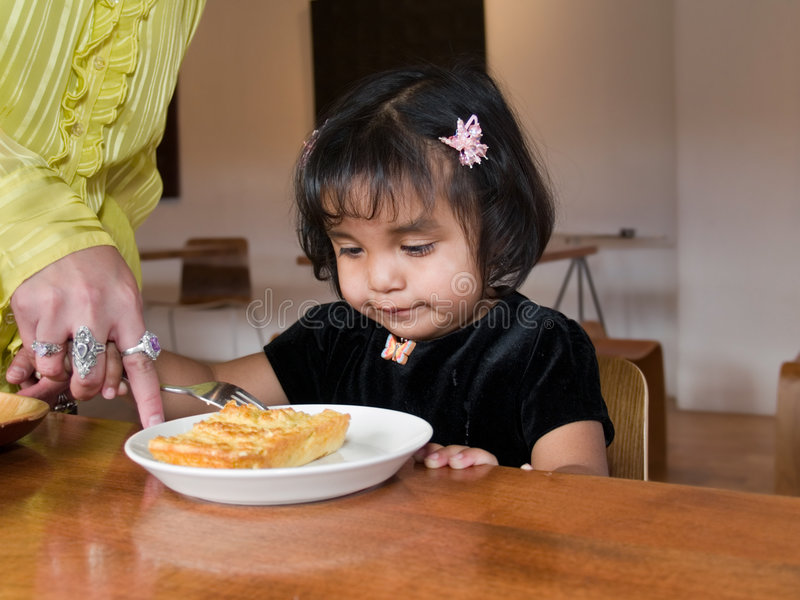 Little Native American girl eating quiche stock photo