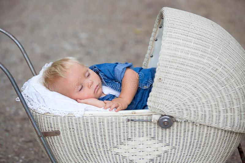 Little newborn baby boy, sleeping in old retro stroller in fores. T, autumn time. Posed baby in retro pram, baby sleeping, vintage stroller stock photo