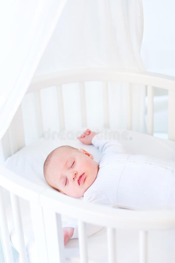 Little newborn baby boy sleeping in white round crib. Little newborn baby boy sleeping in a white round crib with canopy stock photos