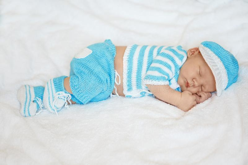 Little newborn baby in a funny hat sleeping in white blanket, lying on bed. stock photography
