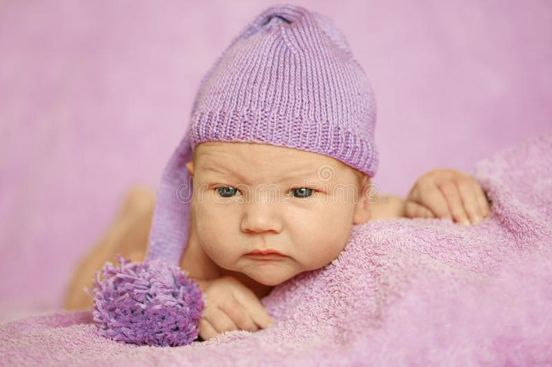 Little newborn baby in a funny hat sleeping in white blanket, lying on bed. stock image