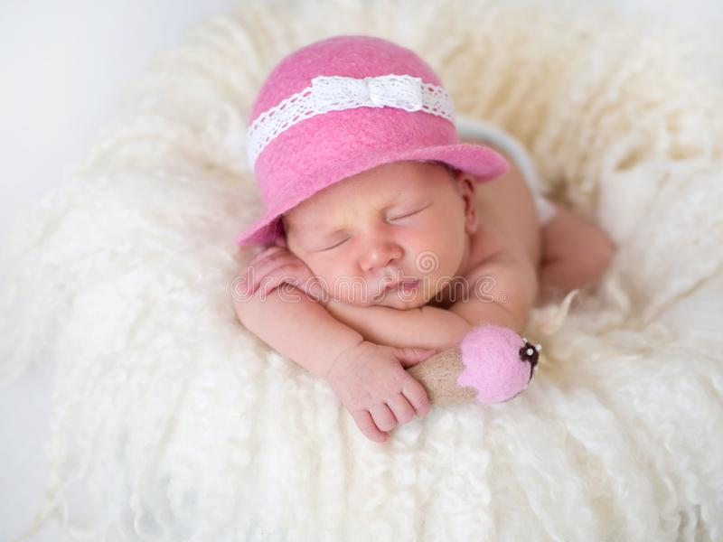 Fashionable newborn baby in a pink hat close-up. Little newborn baby in a pink hat and with ice cream in her hands sleeps arms folded under her cheeks royalty free stock image