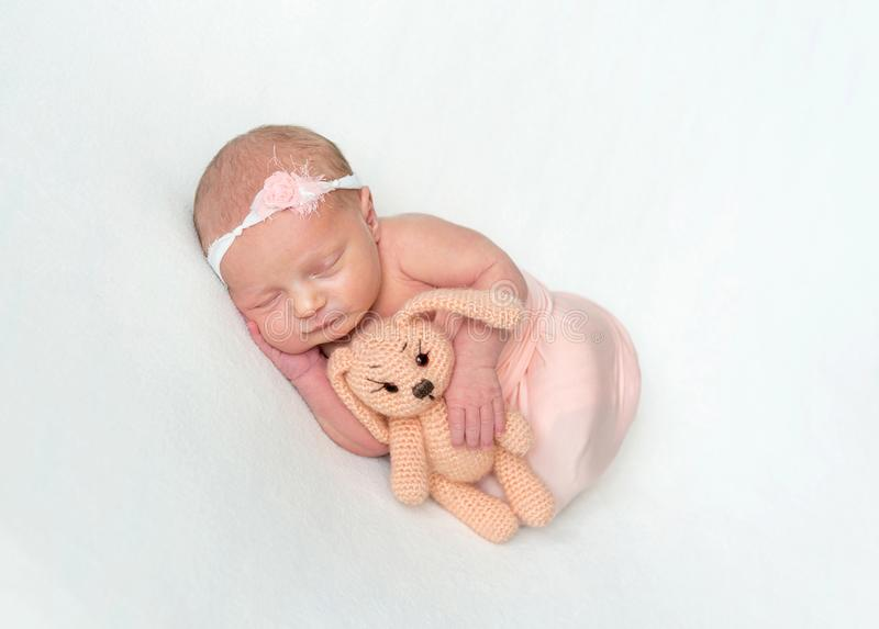 Newborn girl sleeping and cuddling toy royalty free stock image