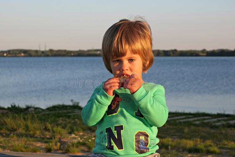 Little nice boy eating pancakes. A small picnic by the river. royalty free stock photos