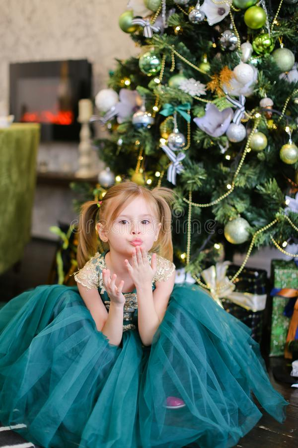 Little nice girl wearing blue dress standing near Christmas tree. royalty free stock images