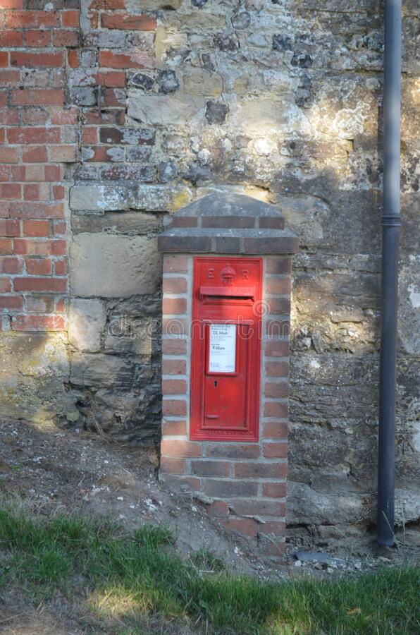 Little old Red Postbox in a Farm Wall royalty free stock photography