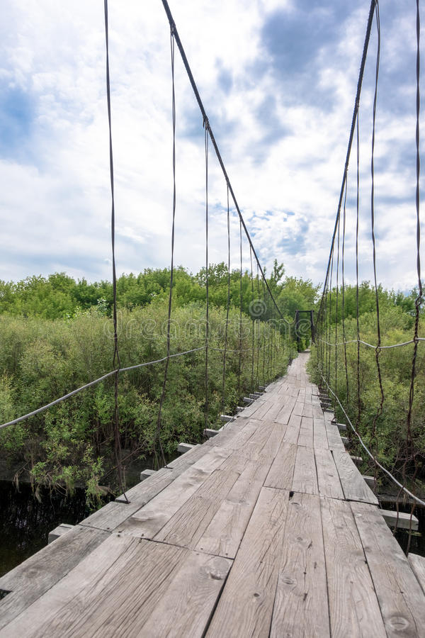 Little old wooden bridge in the village. Little old wooden suspension bridge in the village among the green trees in daylight saving time royalty free stock photo