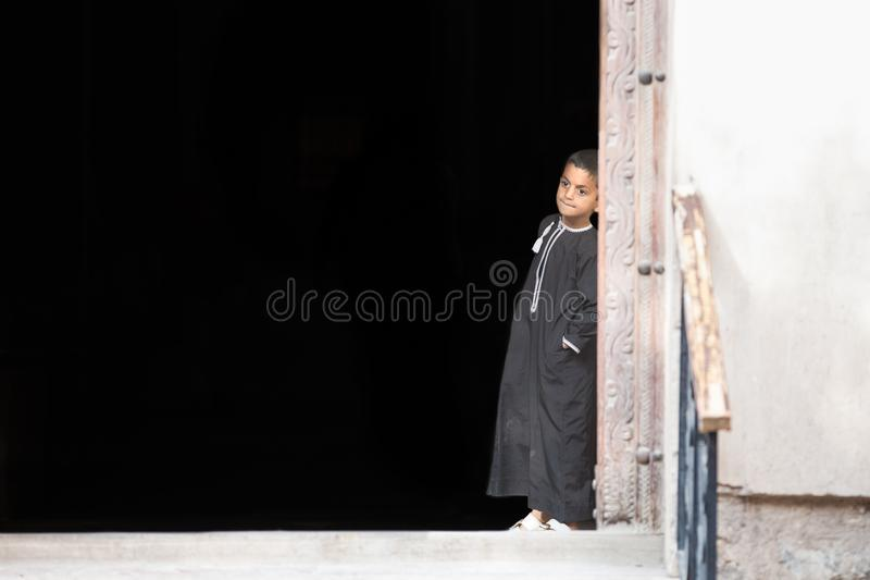 Little Omani boy leaning against a wall. stock photo