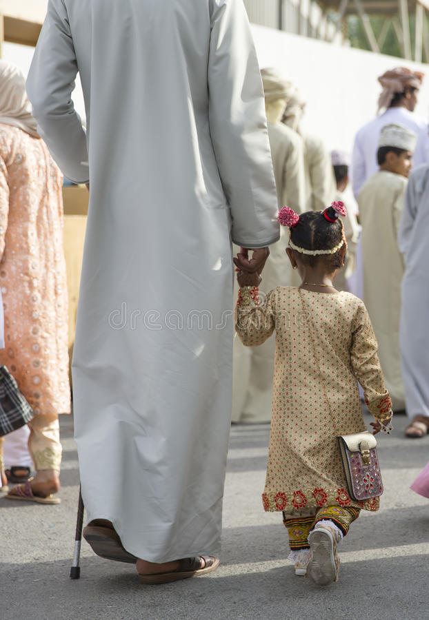 Little Omani girl in traditional clothing walking holding a hand stock photos
