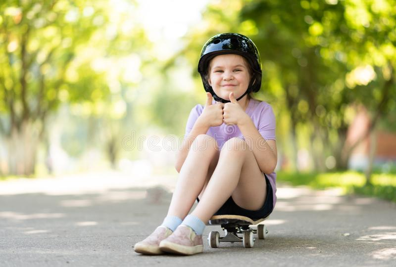 The little one sits on a skateboard, shows a class sign, with a funny expression on her face. For any purpose stock photos