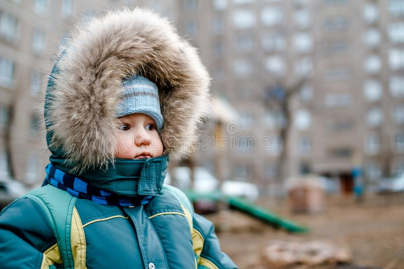 Little one-year-old child in a hood with fur and scarf on the Playground. Outdoors stock photo