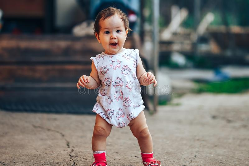 Little one year old girl with dark hair play on yard at home. half-breed girl father is kazakh mother russian caucasian.  stock image