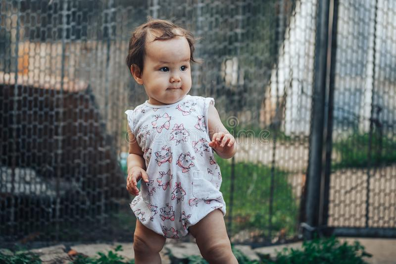 Little one year old girl with dark hair play on yard at home. half-breed girl father is kazakh mother russian caucasian.  stock photos