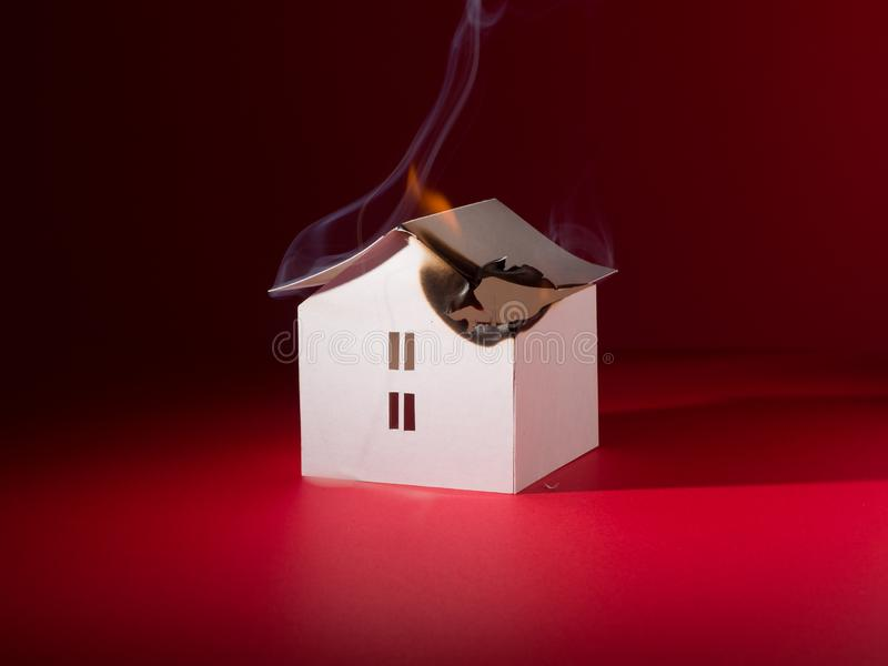 The little paper house model is burning. Allegory of a building fire, accident royalty free stock image