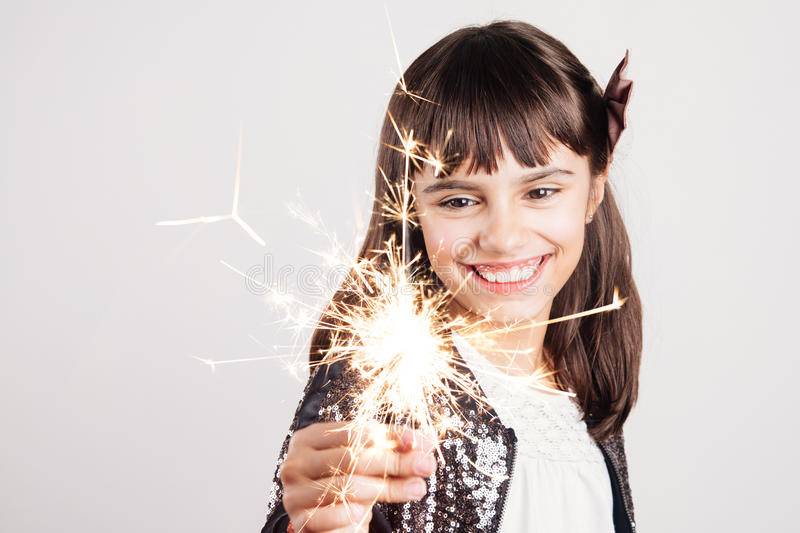 Little party girl holding a sparkler. Happy little girl in sequins dress holding a sparkler enjoying the party royalty free stock photo