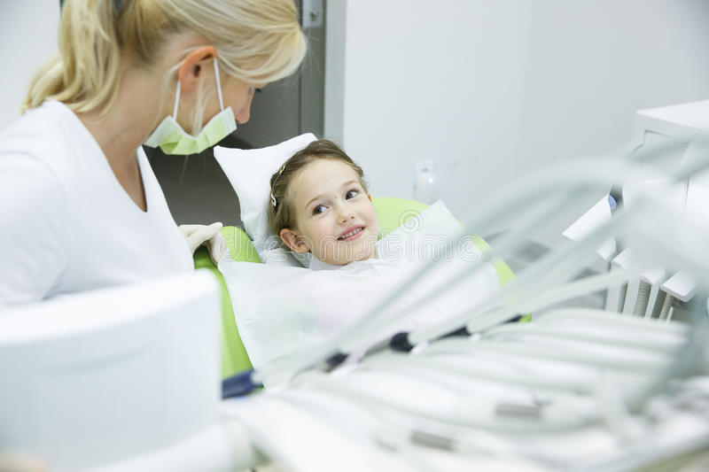 Little patient conversing with her dentist. At dental office before her regular checkup for caries and gum disease. Early prevention, oral hygiene and milk royalty free stock photography